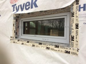 One of the north windows with exterior taping complete (top of window flashing remains)